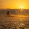 気嵐に包まれた冬の雨晴海岸、富山湾越しの立山連峰と日の出