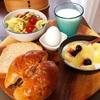 今日の朝食ワンプレート、どんぐりのくるみあんパン、胚芽パン ・牛乳、ベーコンとレタスのサラダ、りんごバナナブルーベリーヨーグルト