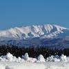 道路わきには雪の山 向こうには月山