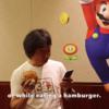 宮本茂、ハンバーガーを食べながらマリオをする。