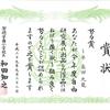 九龍は夏休みの自由研究展の努力賞の賞状と盾をもらう。