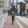 暖かい日、みなさん散歩に。ほっつき歩く老人たちの後ろ姿。