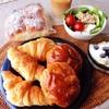 豆パン、クロワッサン、牛乳パン、温玉サラダ、バナナブルーベリーヨーグルト、アイスコーヒー。