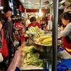 観光客で賑わう六合夜市で蒸しトウモロコシを買う