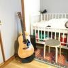 ・ベビーベッド横のアコースティックギターと育児